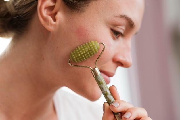 Donna che utilizza un dispositivo per il massaggio del viso lateralmente
