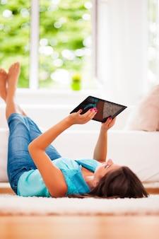 Женщина с помощью цифрового планшета дома