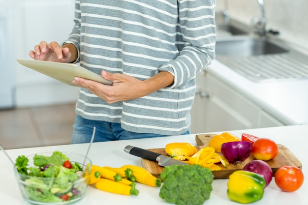 Woman using digital tablet by vegetables in kitchen