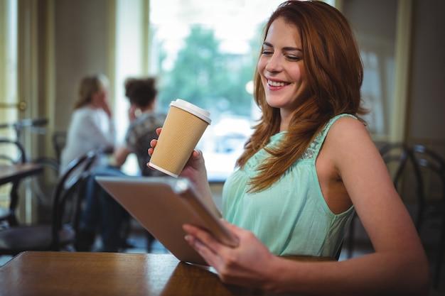 Donna con tavoletta digitale in un caffè