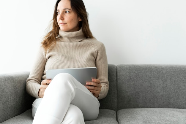 Woman using digital tablet on a couch