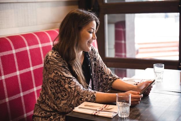 レストランでデジタルタブレットを使用している女性