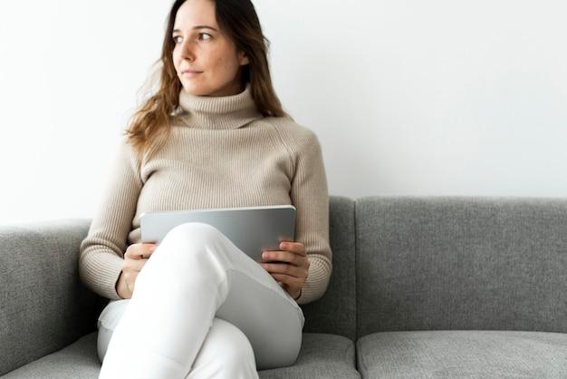 여자 디지털 태블릿을 사용하여 소파