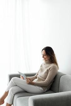 ソファでデジタルタブレットを使用している女性