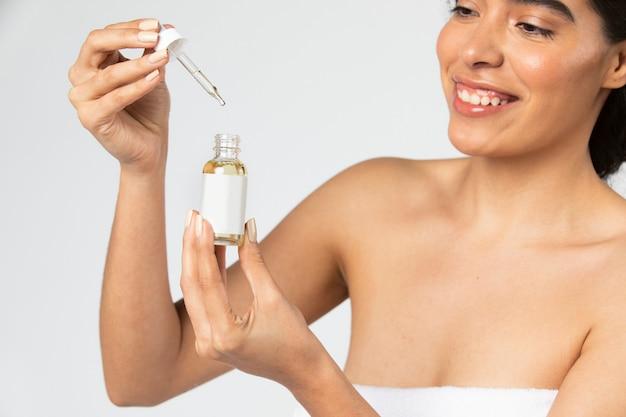 Woman using a a dropper bottle mockup