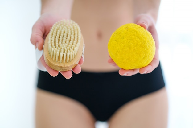 Woman using dry wooden brush for massaging and brushing skin to prevent and treatment cellulite and body problem at home. skin health
