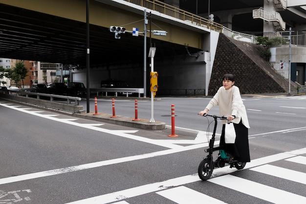 Женщина, использующая электрический велосипед в городе