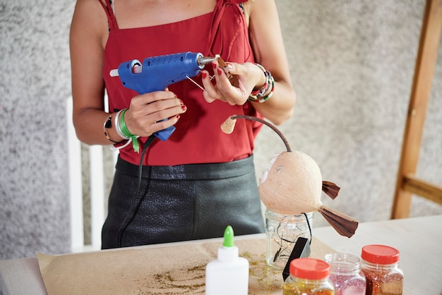 Женщина с помощью электрического клеевого пистолета для работы