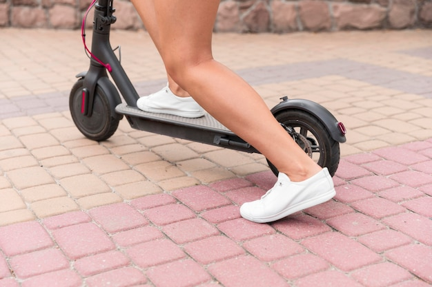 Woman using electric scooter outdoors