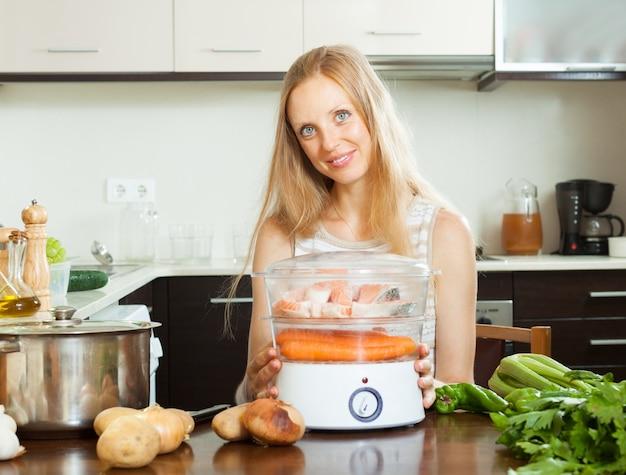 Женщина, используя электрический пароход на кухне дома