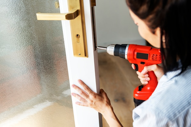 Woman using electronic drill install door