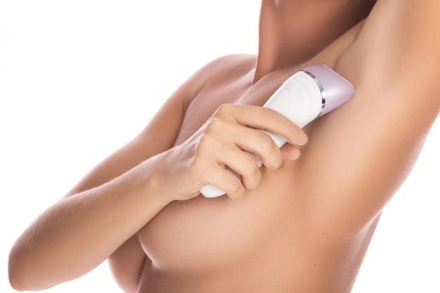 Woman using epilator on her armpit