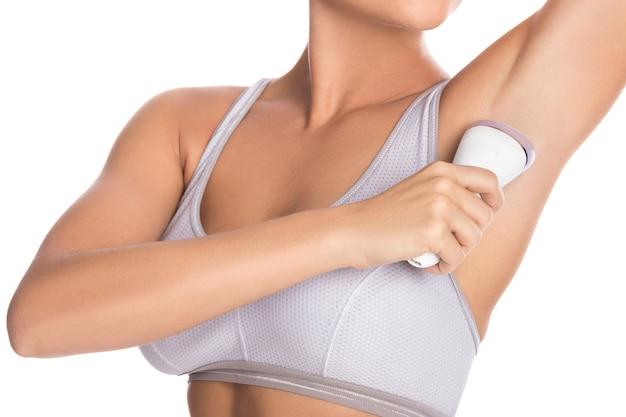 Женщина использует эпилятор на подмышках