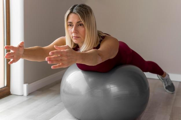Donna che utilizza una palla fitness per i suoi esercizi