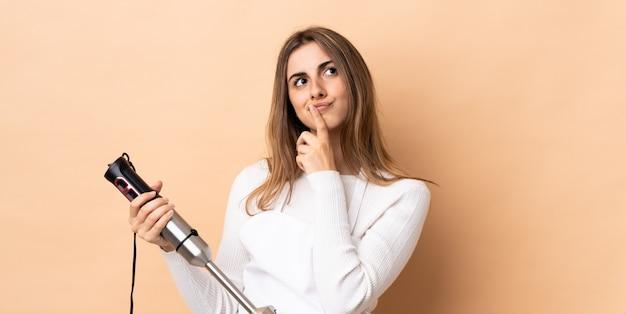 見上げながら疑問を持つ孤立した壁にハンドブレンダーを使用している女性