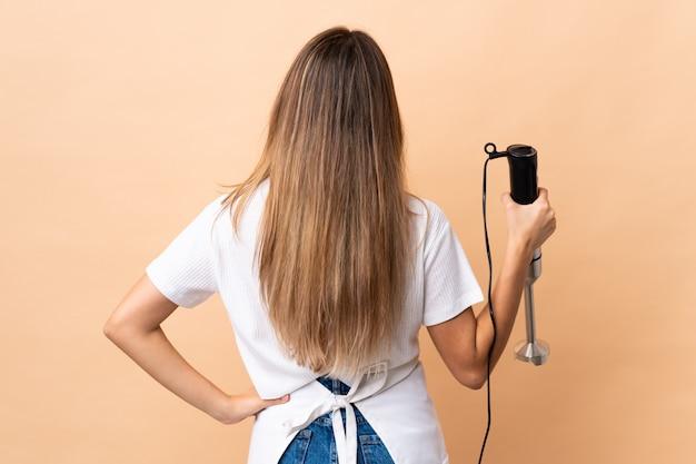 다시 위치에 고립 된 벽에 핸드 블렌더를 사용하는 여자
