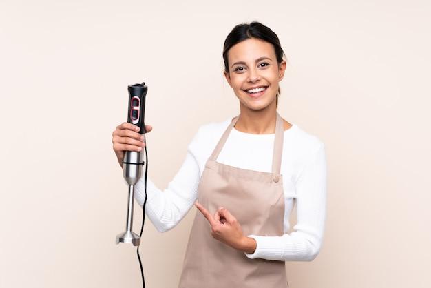 Woman using hand blender and pointing it