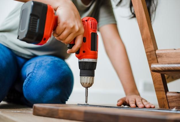 木製のテーブルを組み立てるために手でドリルを使う女性