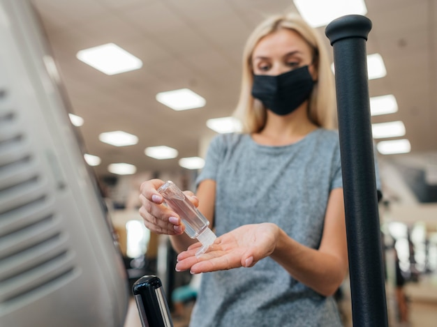 Woman using hand sanitizer at the gym during pandemic