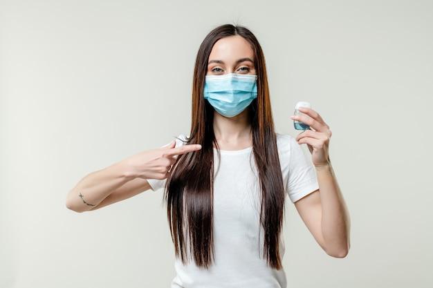 Woman using hand sanitizer wearing mask