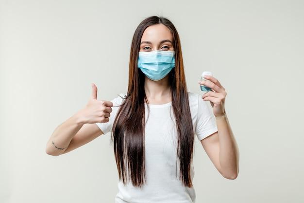 マスクを身に着けている手の消毒剤を使用して女性