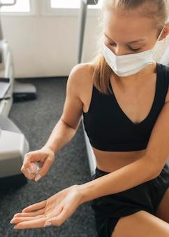 Женщина использует дезинфицирующее средство для рук в медицинской маске в тренажерном зале