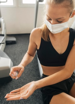 Woman using hand sanitizer while wearing medical mask at the gym