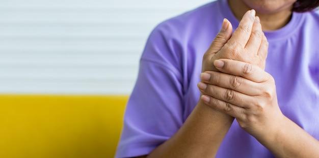 Женщина держит руку другой рукой, чувствуя боль, боль и покалывание. понятие о синдроме гийена-барре и болезни онемевших рук.