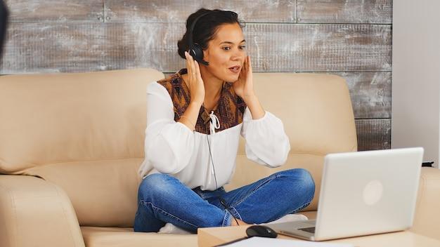 Женщина с помощью наушников общается с слышать коллективную работу во время видеозвонка во время работы из дома.