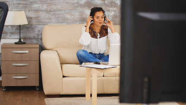 Женщина с наушниками во время видеозвонка во время работы из дома, сидя на диване в гостиной.