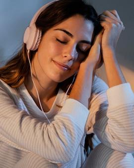 Женщина, использующая наушники для музыки дома в постели