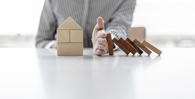나무 블록이 집 모양의 나무 블록에 떨어지는 것을 방지하기 위해 손을 사용하는 여성, 높은 가격을 절약할 수 있는 위험을 방지하기 위한 보험, 주택 보험 아이디어.