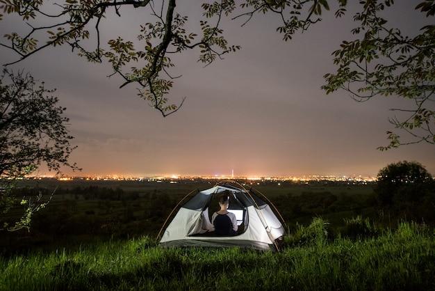 夜のキャンプで彼女のラップトップを使用している女性