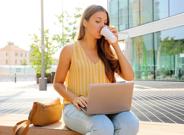 屋外に座って彼女のラップトップを使用している女性