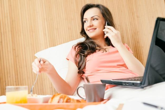 携帯電話を使って朝食をとっている女性。彼女は寝室にいます
