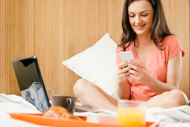 Женщина с помощью мобильного телефона и завтрака. она в спальне