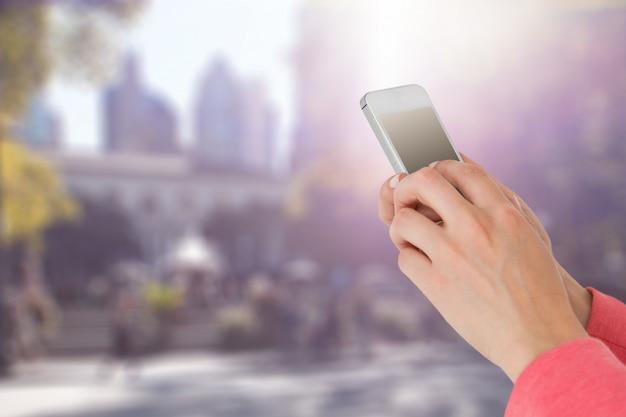 Donna con il suo telefono cellulare su sfondo sfocato