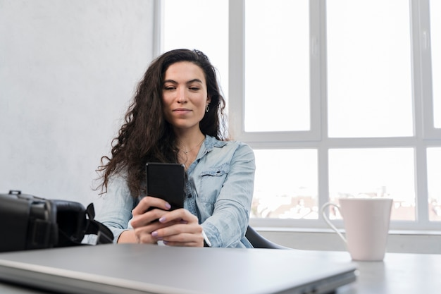 Woman using her mobile phone in a business office