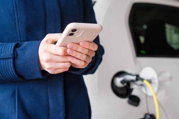 Женщина, использующая свой мобильный телефон на фоне зарядки электромобиля на парковке