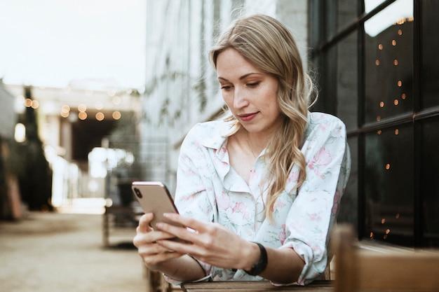 Женщина, использующая свой телефон в кафе