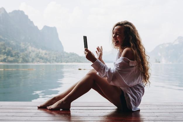 女性は湖で彼女の電話を使用して