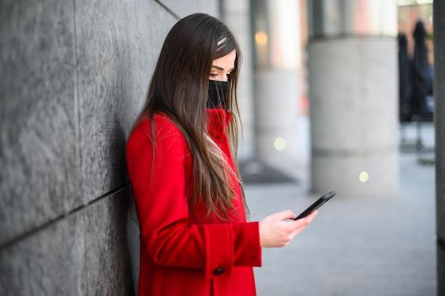 Женщина использует свой смартфон в защитной маске от пандемии коронавируса covid 19