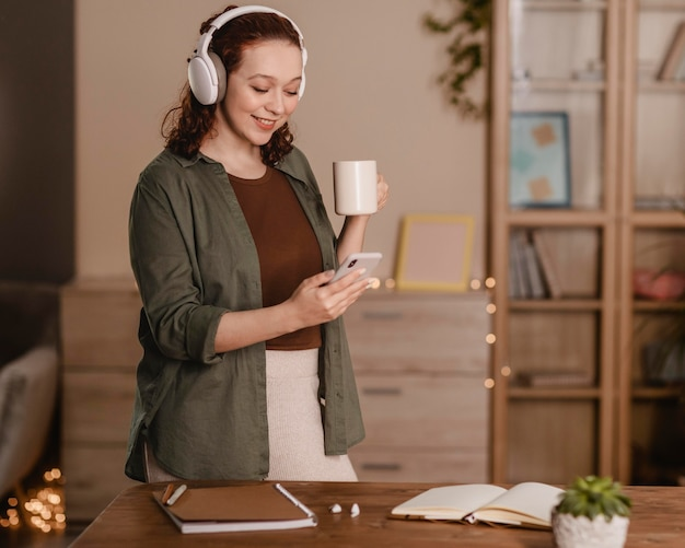 Женщина, использующая свой смартфон и наушники дома за чашкой кофе
