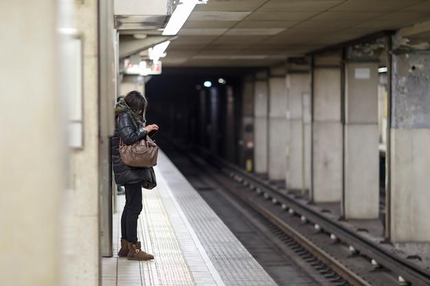 Woman using her smartphone on platform