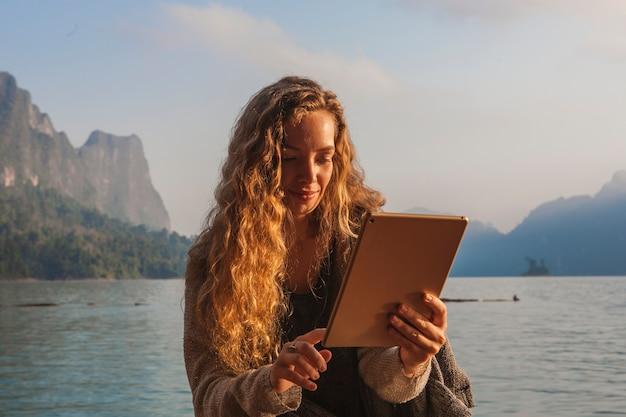 Женщина, используя ее таблетку у озера