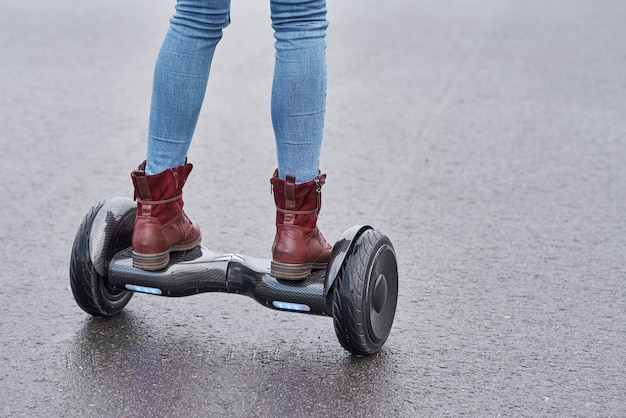 Woman using hoverboard on asphalt road