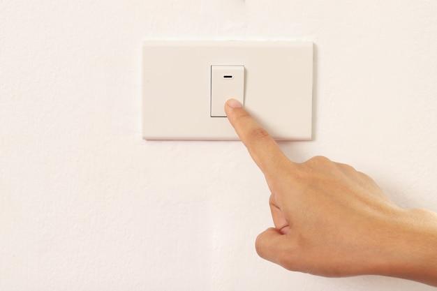 人差し指を使って電気を消す女性