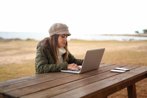 ラップトップで働いている海の公園の木製のテーブルに座って、屋外でインターネット接続を使用している女性