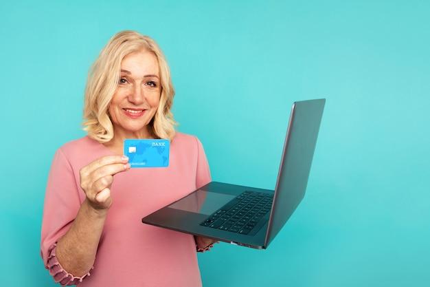 コンピューターとクレジットカードでオンラインショッピングにインターネットを使用している女性。