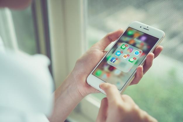 Woman using iphone displays app social